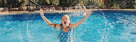 Cute adorable girl swimming splashing in pool on home backyard. Kid child enjoying having fun in swimming pool. Summer outdoors water activity for kids. Web banner header.