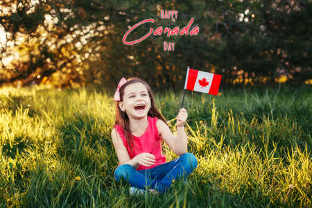 Happy Canada Day. Greeting card with text. Caucasian smiling laughing girl holding Canadian flag. Happy child waving Canada flag in park. Kid citizen celebrating Canada Day holiday outdoors.