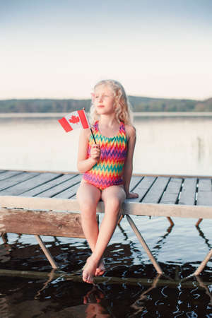 Happy Caucasian girl sitting on dock pier by lake and waving Canadian flag. Smiling child holding Canada flag sitting by water. Kid citizen celebrating Canada Day holiday on first day of July outdoors