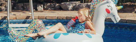 Cute adorable girl in sunglasses with drink lying on inflatable ring unicorn. Kid child enjoying having fun in swimming pool. Summer outdoors water activity for kids. Web banner header. Archivio Fotografico