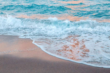 Sea ocean wave water with white foam. Sea sandy beach outdoors. Natural water aquatic blue turquoise aquamarine colorful background. Natural organic ecological environmental texture wallpaper. Archivio Fotografico