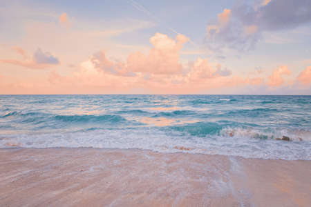 Sea ocean beach sunset sunrise landscape outdoors. Water wave with white foam. Beautiful sunset airy red sky with clouds. Natural aquatic blue pink turquoise aquamarine colorful background.