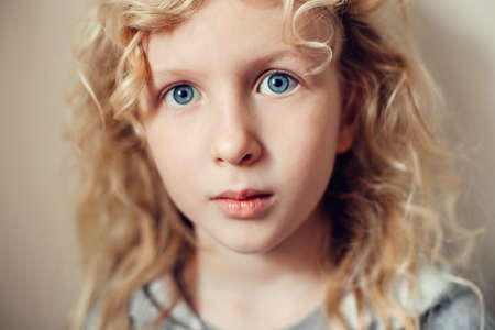 Closeup portrait of beautiful pensive serious Caucasian blonde girl with long hair on light neutral beige background. Pretty real girl child with natural emotion. Happy authentic childhood lifestyle.