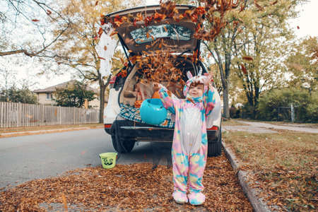 Trick or trunk. Happy baby in unicorn costume throwing leaves and celebrating Halloween in trunk of car. Cute smiling toddler preparing for October holiday outdoors. Safe alternative celebration.