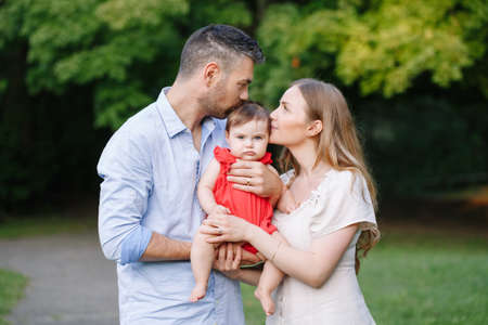 Family day. Caucasian mother and father kissing baby daughter in park. Happy family mom, dad and little girl together outdoor on summer day. Authentic lifestyle real people.