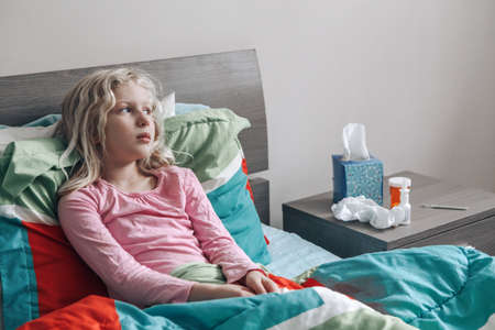Sick ill Caucasian girl with fever lying in bed at home. Virus cold season flu illness. Medicine and health concept. Sick sad upset unhappy child sitting at home indoor with fever disease.