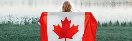 Girl wrapped in large Canadian flag by Muskoka lake in nature. Canada Day celebration outdoors. Kid in large Canadian flag celebrating national Canada Day on 1 of July. Web banner header.