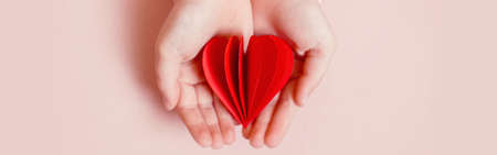 Closeup of child kid hands holding red paper folded heart on light pink background. Valentines Day holiday. Support, care and love concepts. Web banner header. Archivio Fotografico