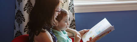 Mother with son boy reading book together. Child kid early development education literacy. Family mom and baby spending time together at home. Homeschooling concept. Web banner header.