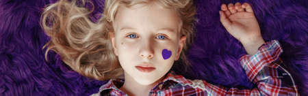 International world epilepsy illness awareness day. Cute pretty blonde Caucasian girl with small violet purple paper heart on cheek lying on purple fluffy rug carpet at home. Web banner header.
