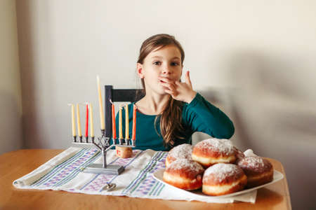 Kid eating sufganiyot donuts, sweet festive food. Girl with menorah for a traditional winter Jewish Hanukkah holiday. Child celebrating Chanukah festival of lights at home. Israel holiday.