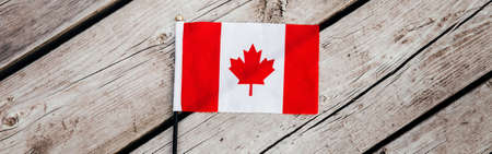 Red Canadian flag with red maple leaf on wooden planks background outdoors. Canadian flag symbol during Canada Day national celebration on July 1. View from top above. Web banner header.