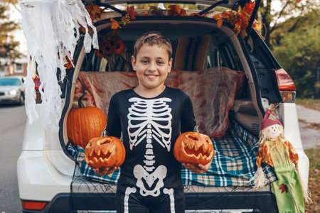 Trick or trunk. Boy child with red carved pumpkins celebrating Halloween in trunk of car. Happy kid preparing for October holiday outdoors. Social distance and safe alternative celebration.