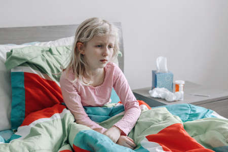 Sick ill Caucasian girl with fever lying in bed at home. Virus cold season flu illness. Medicine and health concept. Sick sad upset unhappy child sitting at home indoors with fever disease.