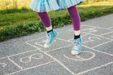 Closeup of chld girl playing jumping hopscotch outdoor. Funny activity game for kids on playground outside. Summer backyard street sport for children. Happy childhood lifestyle. Archivio Fotografico