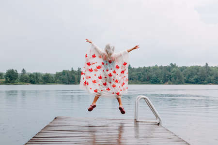 Girl child in rain poncho with red maple leaves jumping on wooden lake dock. Canada Day holiday. Kid raising arms up under rain outdoors. Connection with nature. Freedom and happy childhood lifestyle.