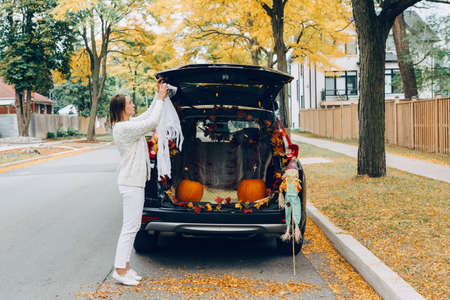 Trick or trunk. Halloween in car. Woman decorating vehicle for traditional October holiday outdoors. Red pumpkins, scarecrow, autumn fall leaves for holiday celebration in back of truck van.