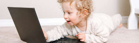 Blond curly toddler baby boy working on laptop. Little kid child using technology. Early age education development. Video chat, video call. Computer screen time for children. Web banner header