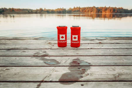 Two cans of beer in red cozy beer can coolers with Canadian flag standing on wooden pier by lake outdoors. Wet footprints on wooden dock. Friends celebrating Canada Day national celebration by water.