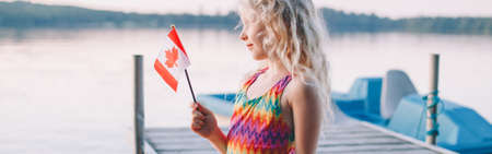 Girl sitting on dock pier by lake and waving Canadian flag. Child holding Canada flag sitting by water. Kid citizen celebrating Canada Day holiday outdoors. Web banner header.