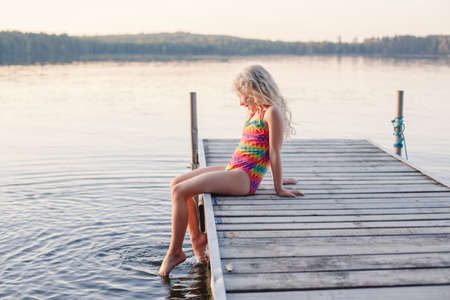 Funny happy cute Caucasian blonde girl child sitting on wooden deck pier by lake. Smiling laughing kid in swimsuit splashing with legs in water. Summer fun outdoors activity. Happy childhood lifestyle Archivio Fotografico
