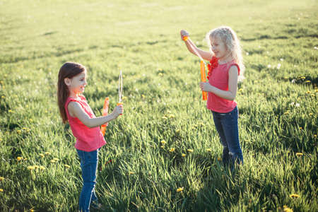 Soap bubbles game. Girls friends blowing soap bubbles in park on summer day. Kids having fun outdoors. Authentic happy childhood magic moment. Lifestyle seasonal activity for children. Standard-Bild