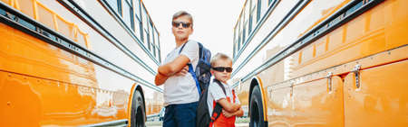 Caucasian brothers students near yellow school bus. Cool kids in sunglasses going back to school in September. Education system and learning. Support and friendship. Web banner header Standard-Bild