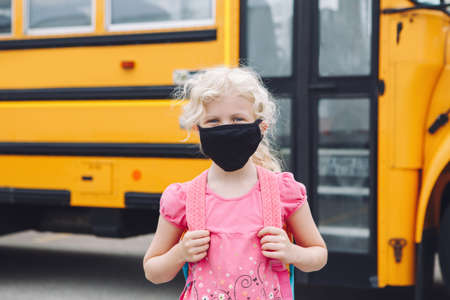 Happy girl student in cloth face mask by yellow school bus outdoors. Kid with personal protective equipment on face. Education and back to school in September. New normal during coronavirus.