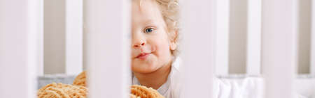 Cute adorable baby boy toddler lying in crib at home. Funny charming baby boy with curly blond hair and blue eyes playing in his bed. Happy authentic candid home life. Web banner header.