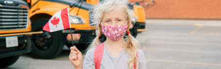 Young girl student in protective face mask with Canadian flag. Student kid by yellow school bus outdoor. Education and back to school. New normal during coronavirus covid-19. Web banner header Standard-Bild