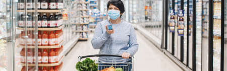 Middle age woman shopping in grocery store supermarket and talking on audio chat phone. New social media chat app. Speaker in live stream on smartphone. Using technology. Web banner header. Standard-Bild