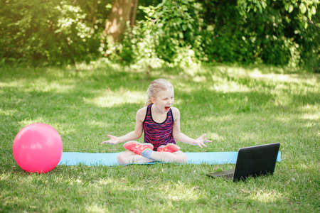 Angry mad girl child doing sport workout outdoors online. Video yoga class on Internet. Funny stressed kid training in park with laptop. New normal. Poor Internet connection Standard-Bild