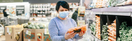 Grocery shopping. Middle age woman with short dark hair in a blue protective face mask buying healthy food vegetables in supermarket.