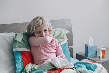 Sick ill girl with fever lying in bed at home with flu, fever, running nose. Child coughing sneezing in elbow.