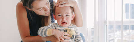 Mother hugging pacifying sad upset crying toddler boy. Family young mom and crying baby sitting on bed at home. Bonding relationship of mom and a child baby. Web banner header. Standard-Bild
