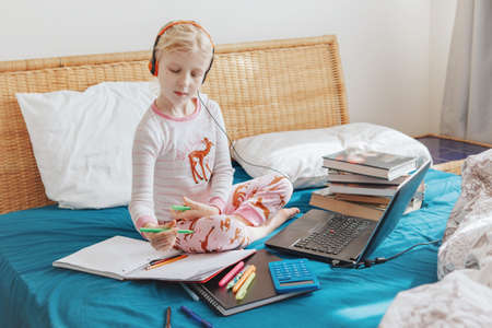 Caucasian girl child sitting in bed and learning online on a laptop Internet. Virtual class lesson on video at quarantine. Distant remote video education. Modern homeschooling study for kids.