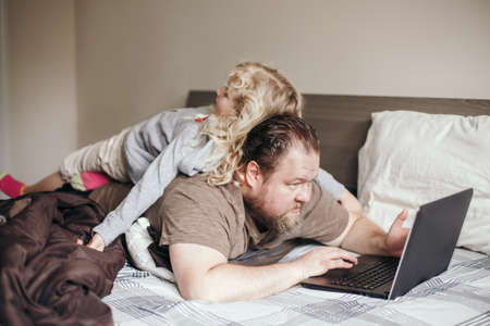 Work from home with kids children. Father working on laptop in bedroom with child daughter on his back.