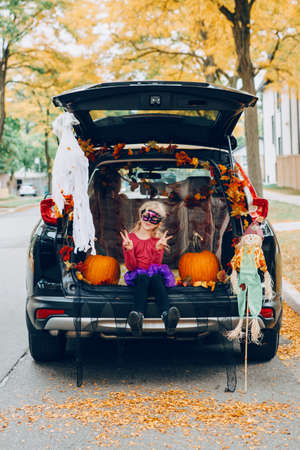 Trick or trunk. Child girl celebrating Halloween in trunk of car. Kid with red pumpkins celebrating traditional October holiday outdoor. Social distance and safe alternative celebration on quarantine. Standard-Bild