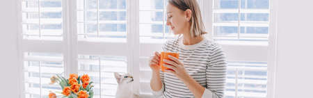 Happy middle age woman drinking coffee and looking at cat. Young woman with short hair drinking tea from mug and playing with pet. Relax and leisure time at home. Web banner header. Standard-Bild
