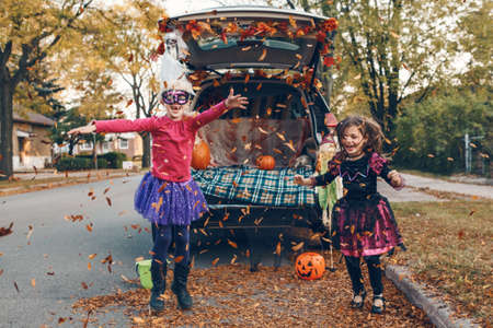 Trick or trunk. Children siblings sisters celebrating Halloween in trunk of car. Friends kids girls preparing for October holiday outdoors. Social distance and safe alternative celebration.