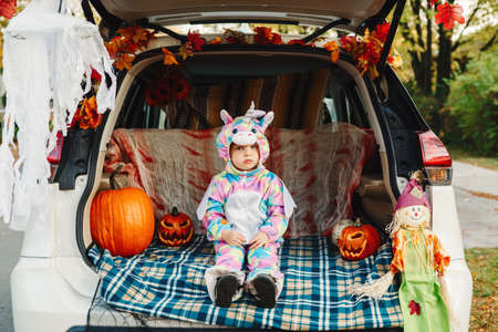 Trick or trunk. Sad upset baby in unicorn costume celebrating Halloween in trunk of a car. Cute toddler celebrating October holiday outdoor. Social distance and safe alternative celebration.