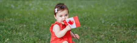 Caucasian baby toddler girl in red dress waving Canadian flag in park outdoors. Kid child citizen sitting on ground in park and celebrating Canada Day on 1st of July. Web banner header.