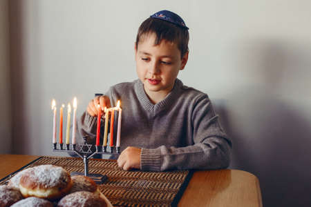 Boy in kippah lighting candles on a menorah for traditional winter Jewish Hanukkah holiday. Child celebrating Chanukah festival of lights at home. Religious Hebrew Judaic Israel culture holiday Standard-Bild