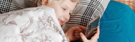 Girl lying in bed in morning and texting talking at social media on a smartphone cellphone. Child kid typing messaging on mobile phone. Chat talk with friends online on Internet. Web banner header. Standard-Bild