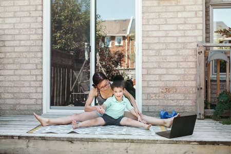 Family sport activity. Middle age Caucasian mother with toddler son doing distant remote online fitness workout on house backyard with laptop. Parent exercising with child boy kid. Sport at home.