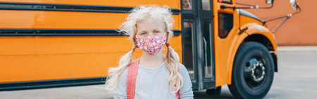 Girl student wearing face mask standing by a yellow bus. Kid with personal protective equipment on face. Education and back to school. New normal during . Web banner header.