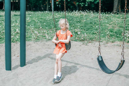 Sad unhappy girl is swinging on swing set in park outdoor alone. Upset bored kid waiting for friend on playground. Lonely child is swinging alone in park and missing friend. Negative emotion.