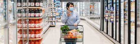 Middle age woman shopping in a grocery store supermarket and talking on audio chat phone. New social media chat app. Speaker in live stream on smartphone. Web banner header. Standard-Bild