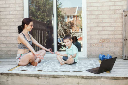 Family sport activity. Middle age Caucasian mother with toddler son doing distant remote online yoga fitness workout on house backyard with laptop. Parent exercising with child boy kid. Sport at home