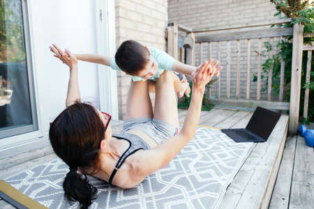 Family sport activity. Caucasian mother with toddler son doing distant remote online fitness workout on house backyard with laptop. Parent mom rocking child on her knees legs. Sport at home